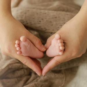 赤ちゃんの足をつかむように手でハート