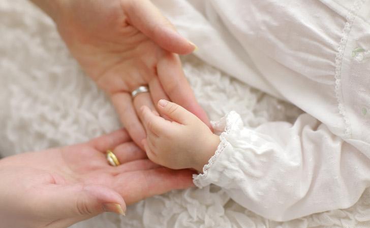 小さな手をそっと支える母の手
